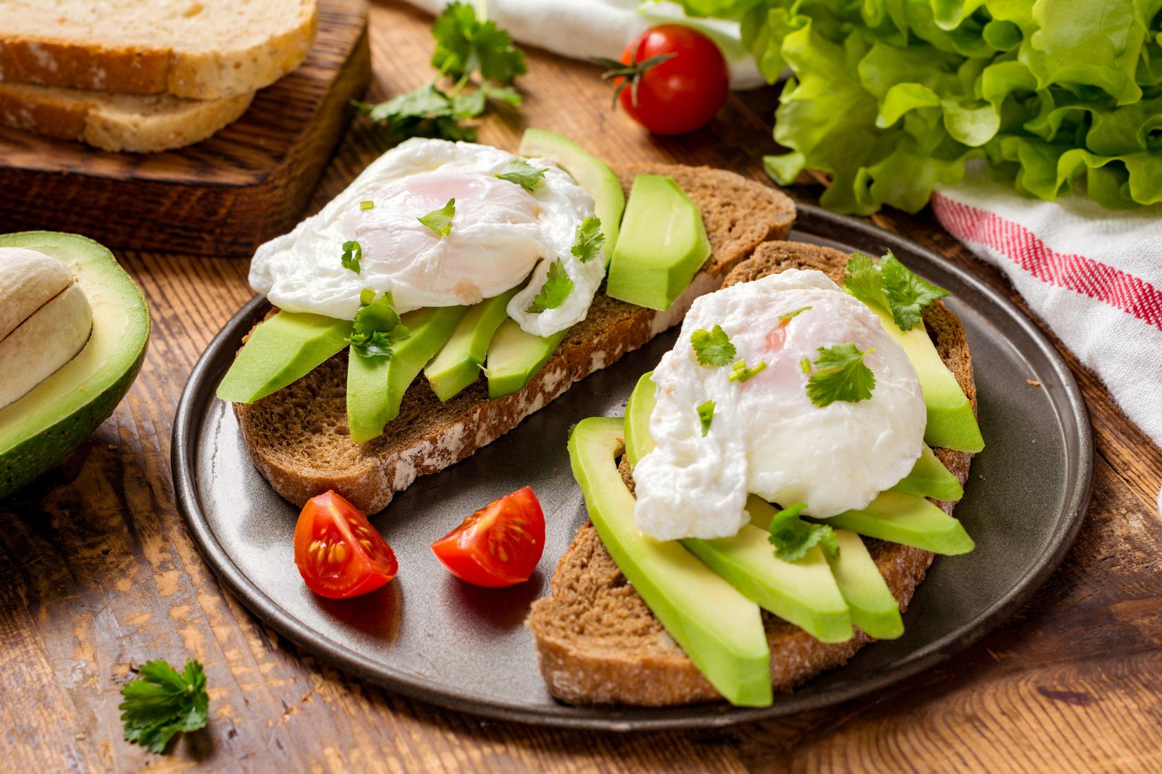 Zwei Scheiben Avocado-Toast mit pochierten Eiern.