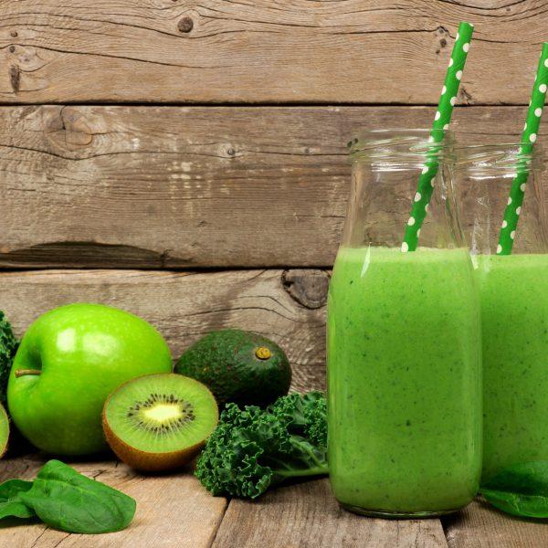 Grüne Smoothies, Obst und Gemüse vor hölzernem Hintergrund.