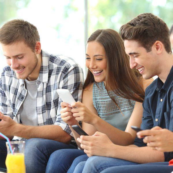 Gruppe junger Menschen sitzt lachend mit Smartphones auf dem Sofa.