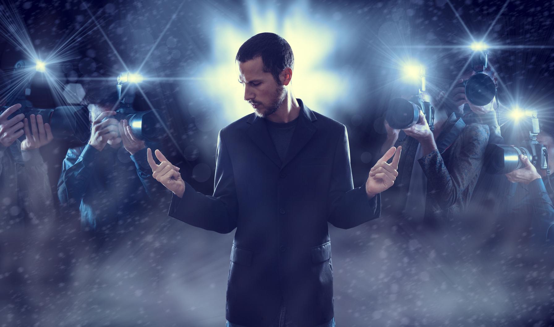 Ein Mann im Blitzlichtgewitter.
