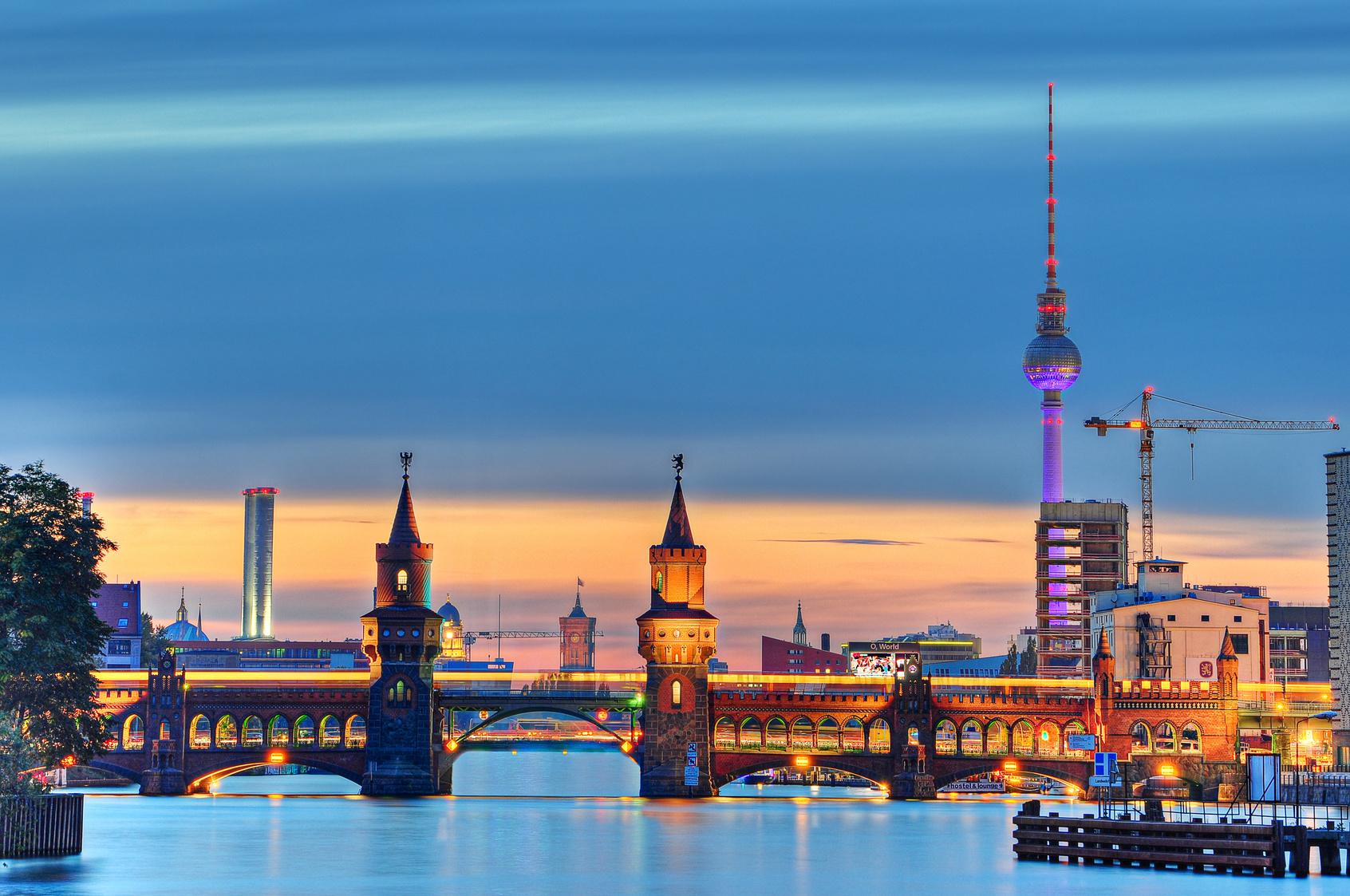 Beleuchtete Oberbaumbrücke in Berlin mit Fernsehturm im Hintergrund.