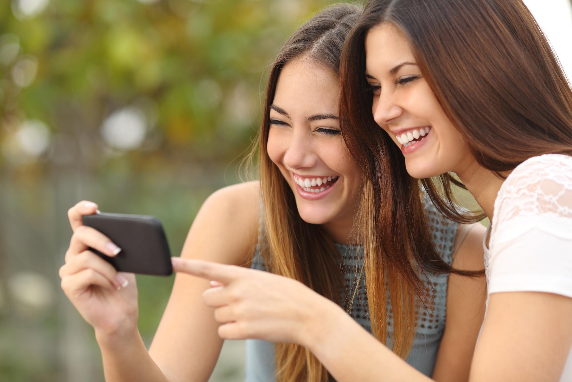 Zwei junge Frauen schauen belustigt auf ein Smartphone.