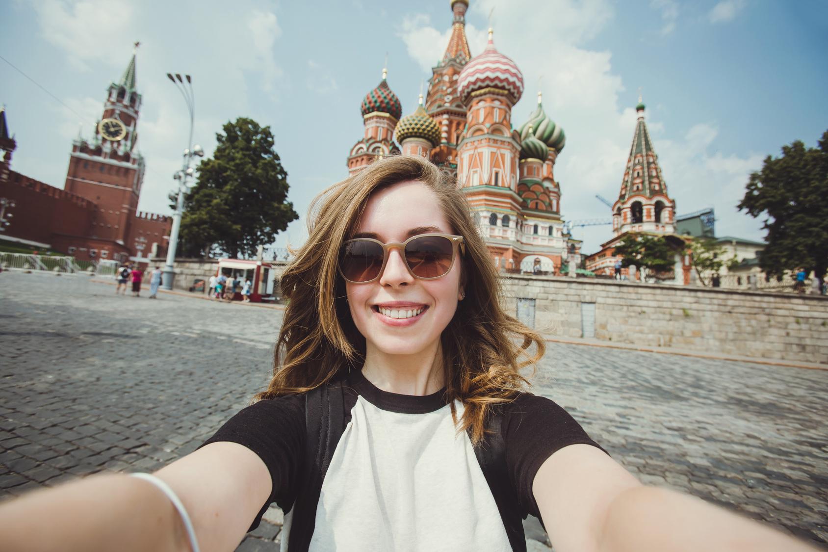 Frau mit Sonnenbrille macht Selfie auf dem Roten Platz in Moskau.