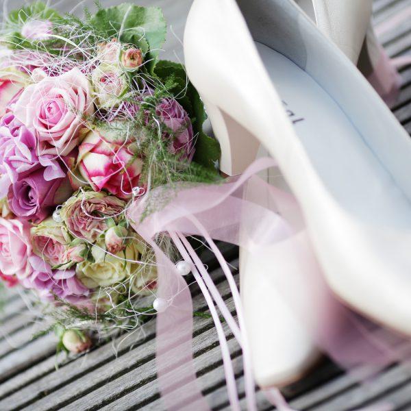 Weiße Brautschuhe neben einem Brautstrauß