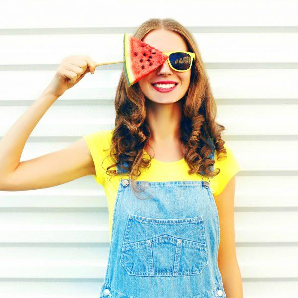 Junge Frau hält sich ein Stück Wassermelone vor ein Auge