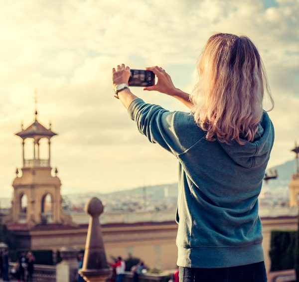 Frau knipst Stadtpanorama mit Smartphone.