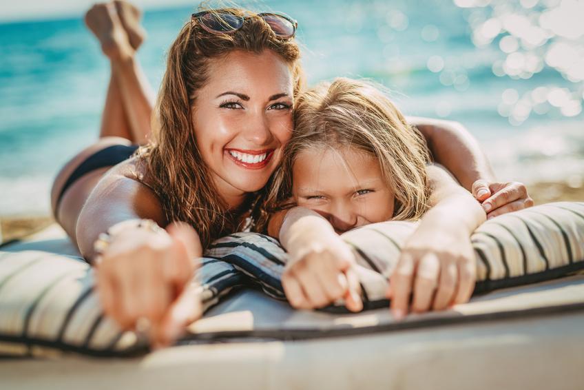 Mutter und Tochter posieren am Strand.