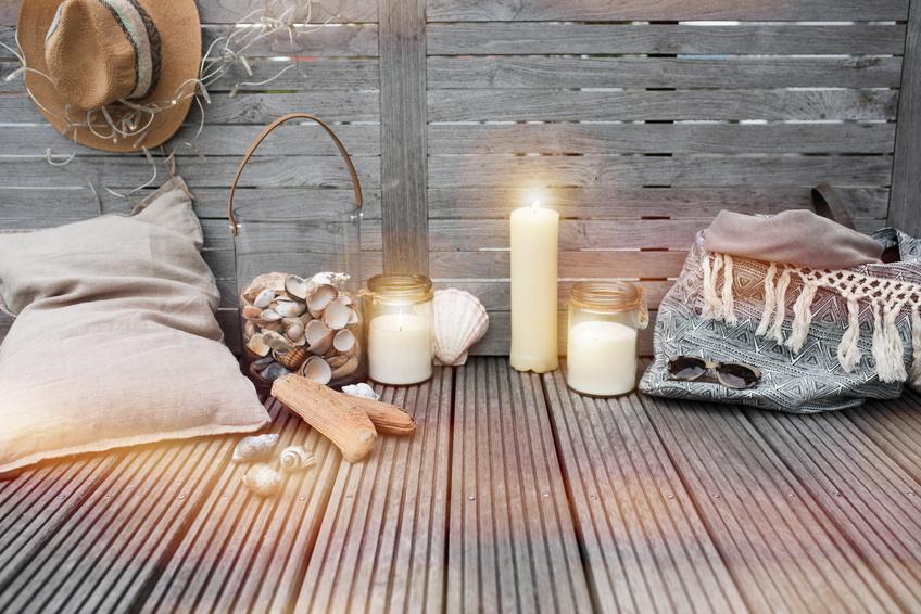 Stillleben aus Kissen, Glas mit Muscheln und Kerzen vor Holzwand