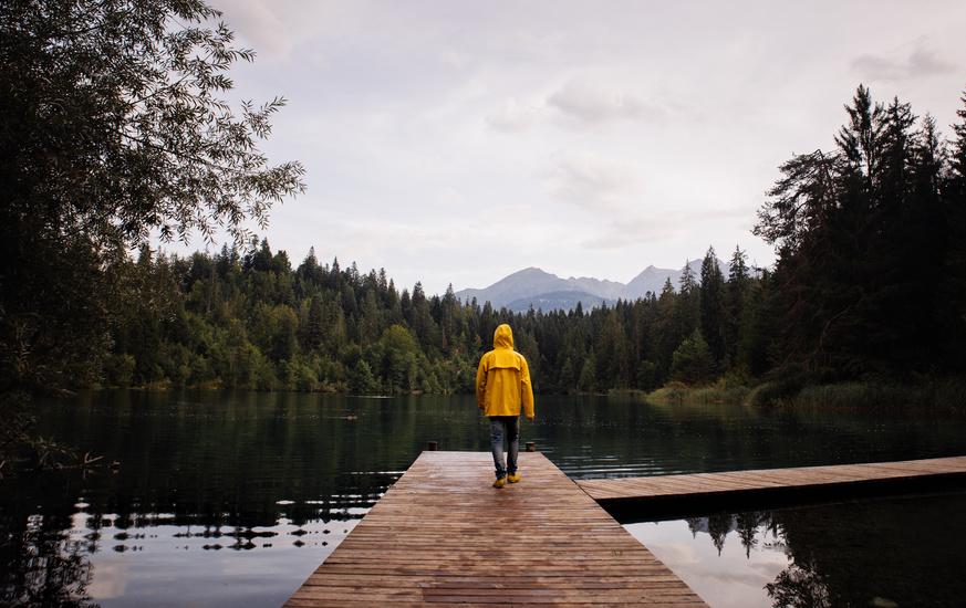 Mann steht auf Steg am See