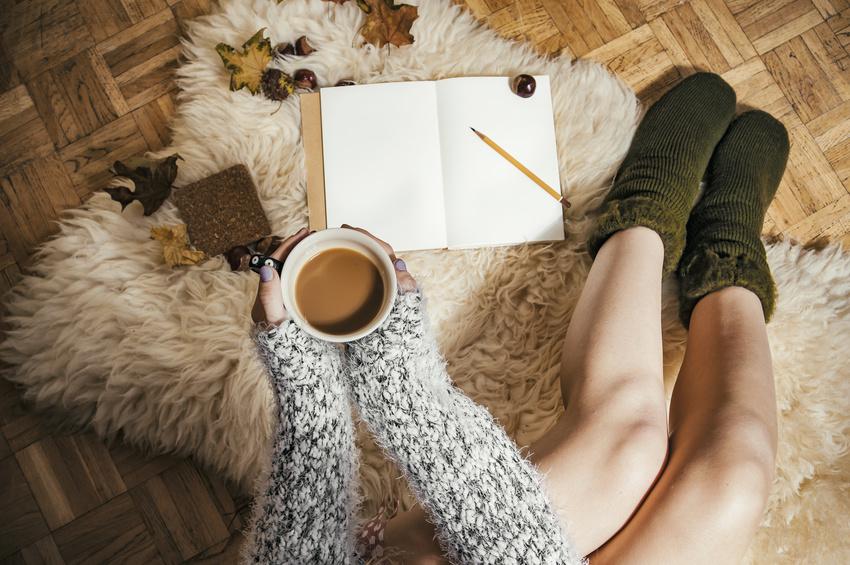 Frau mit Tasse und Buch auf Fellteppich