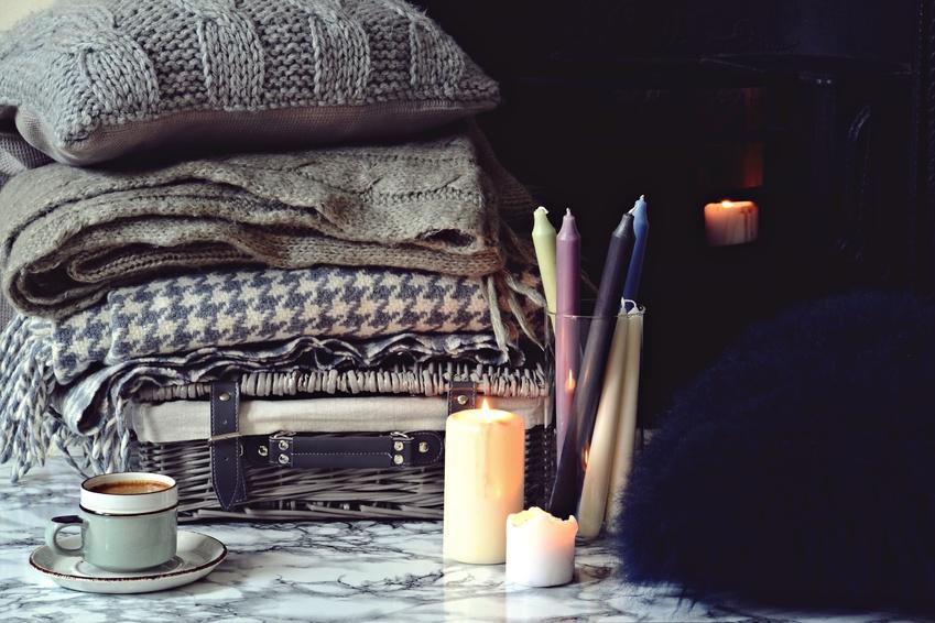 Tasse und Kerzen vor einem Stapel Decken