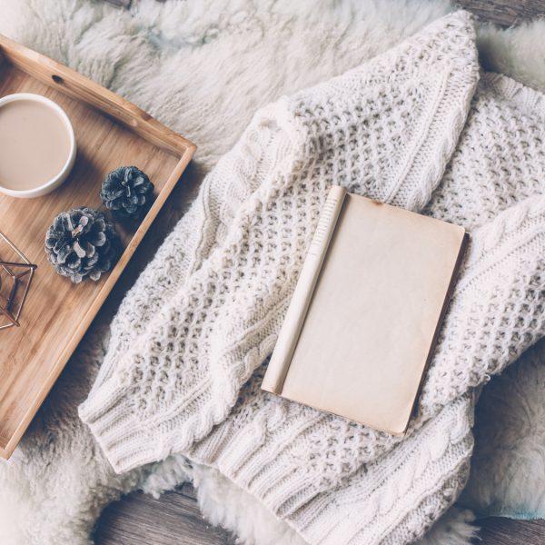 Kaffee, Kerze, Buch und Strickjacke auf Lammfell