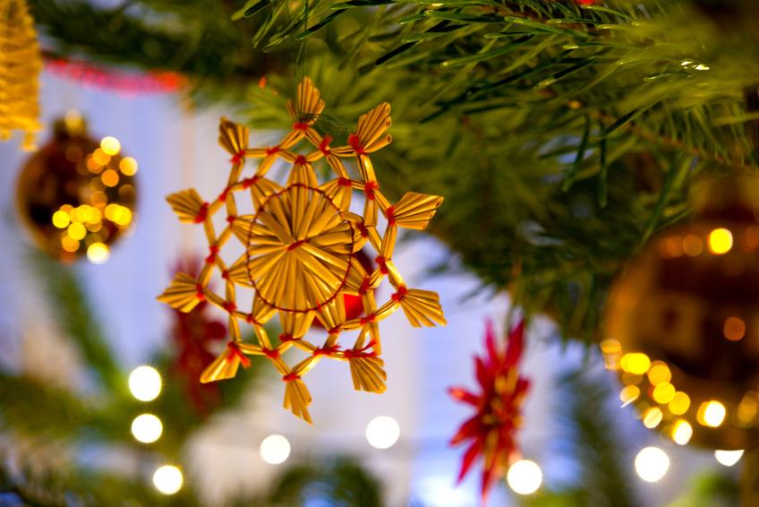 Strohstern, Tannenzweige und Weihnachtskugeln