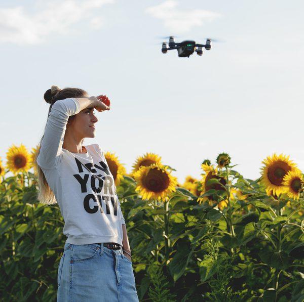 Drohne schwebt über Frau in einem Sonnenblumenfeld
