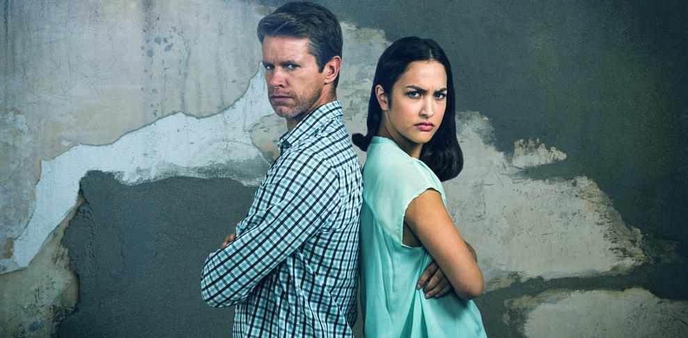 Paar steht Rücken an Rücken vor Wand mit bröckelndem Putz