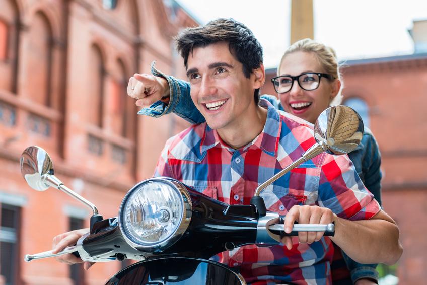 Lachendes Paar auf Motorroller.