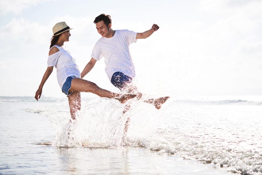 Paar steht knöcheltief im Meer und lässt Wasser mit den Füßen spritzen